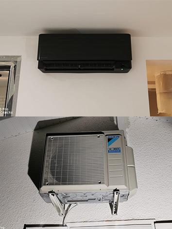 Photo d'un climatiseur daikin noir accroché au mur avec son moteur